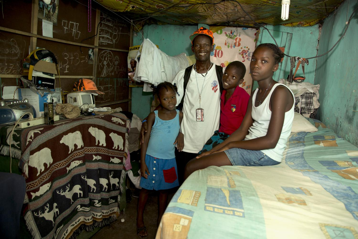 A family of four in their 1 room house in Milot, Haiti.