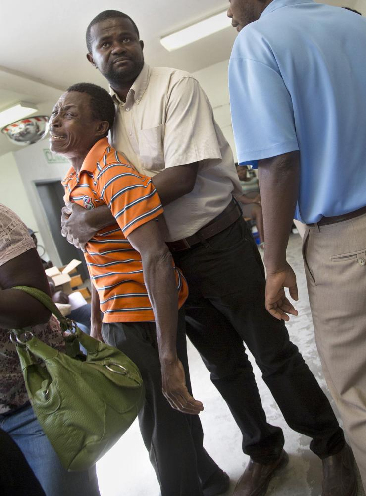 A man learns of his brothers death outside the emergency room at Hospital Sacre Coeur in Milot, Haiti. The death was caused by a motor cycle accident, one of the most common injuries at the hospital.