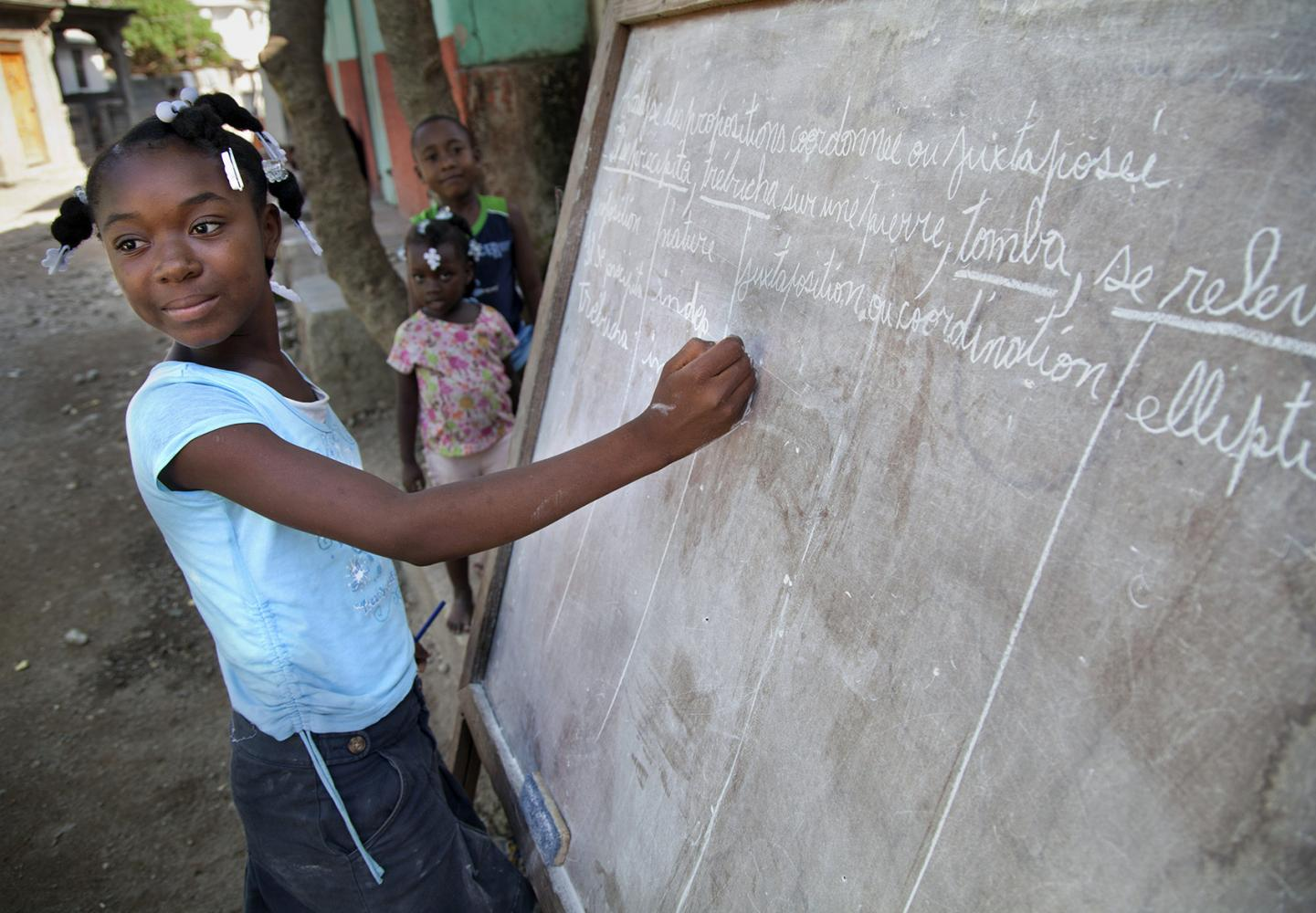 A young girl does school work on a chalk board outside her home in Milot, Haiti.