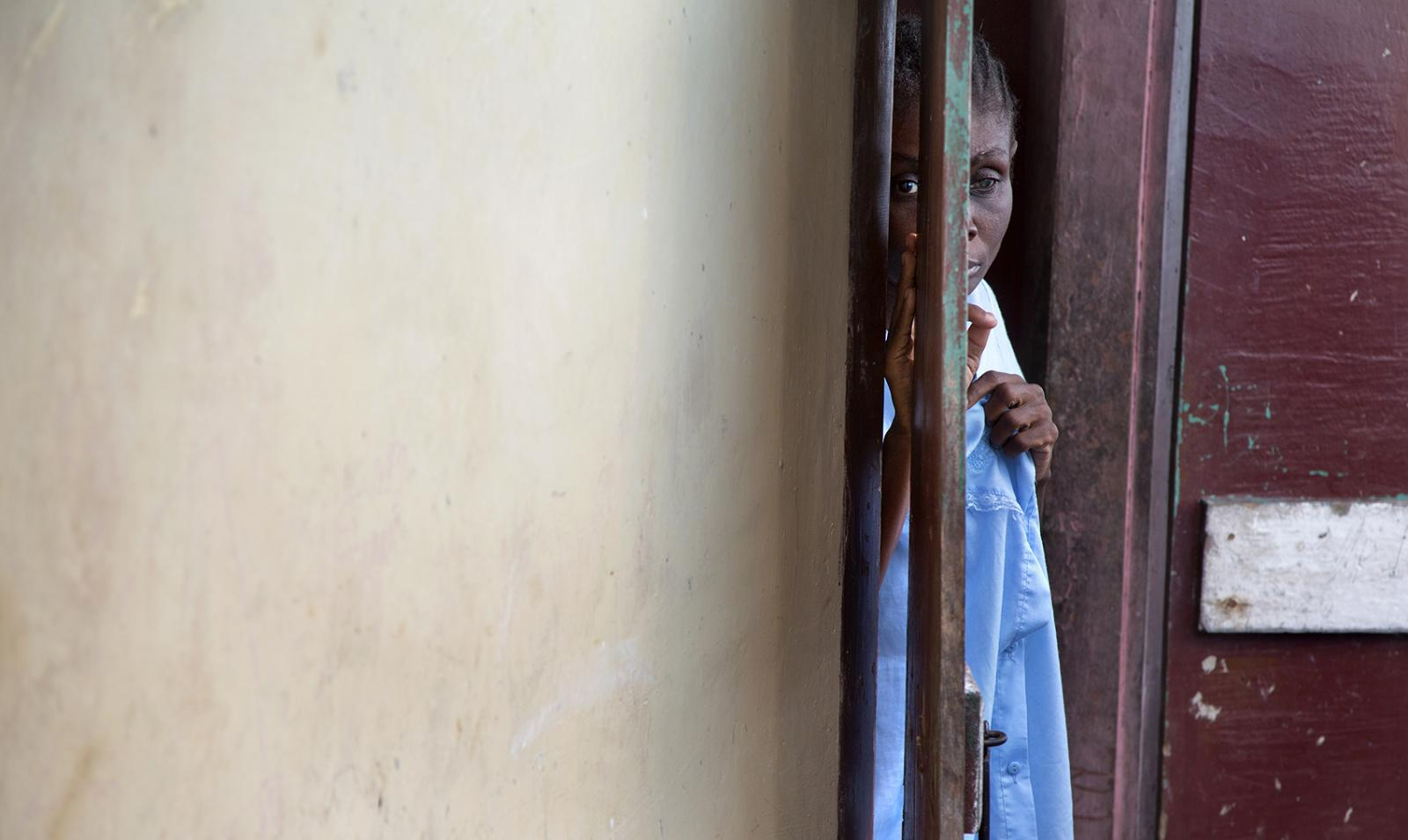 A woman peers through the doorway of her home in Milot, Haiti. She is a breast cancer survivor, which is not common in the area due to lack of early detection.