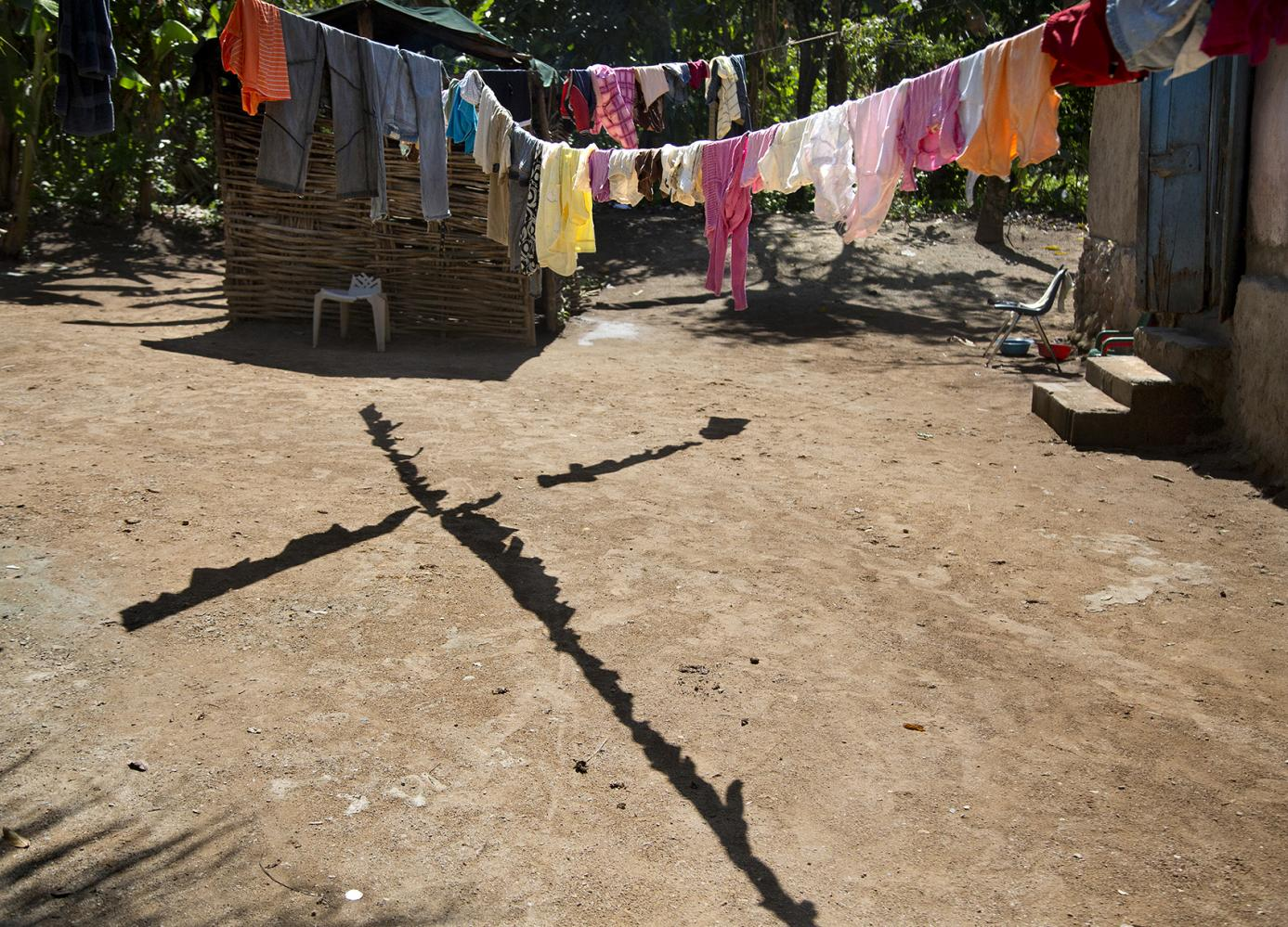 The shadow from drying laundry forms a fiery cross on the ground in Milot, Haiti.