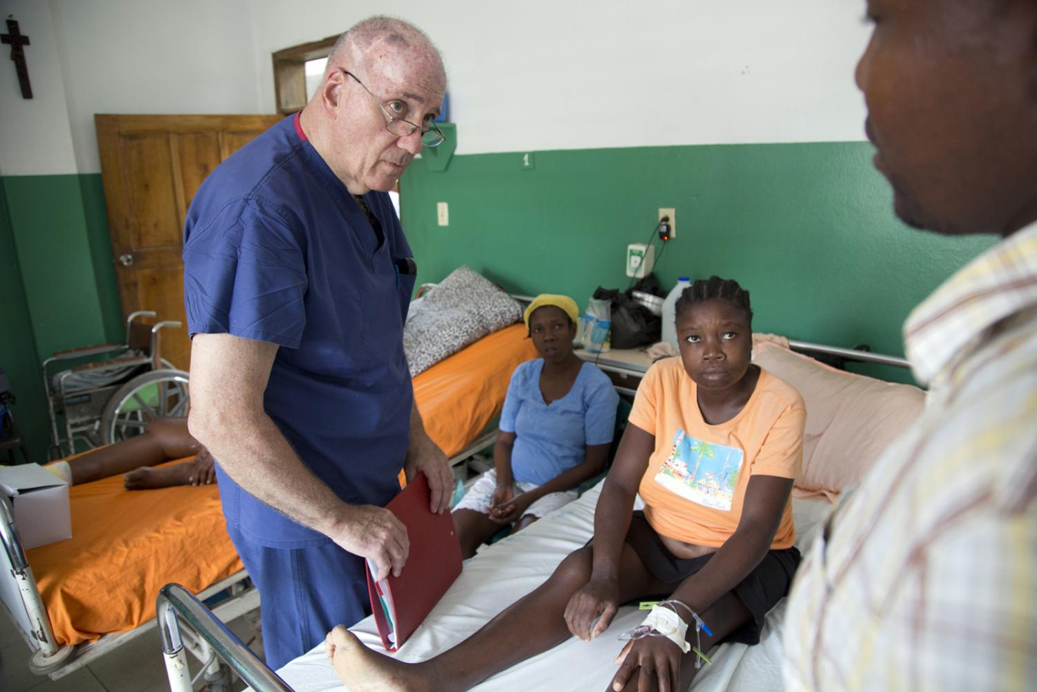 Volunteer American doctor Dave Butler learns about a patient from a translator at Hospital Sacre Coeur in Milot, Haiti.