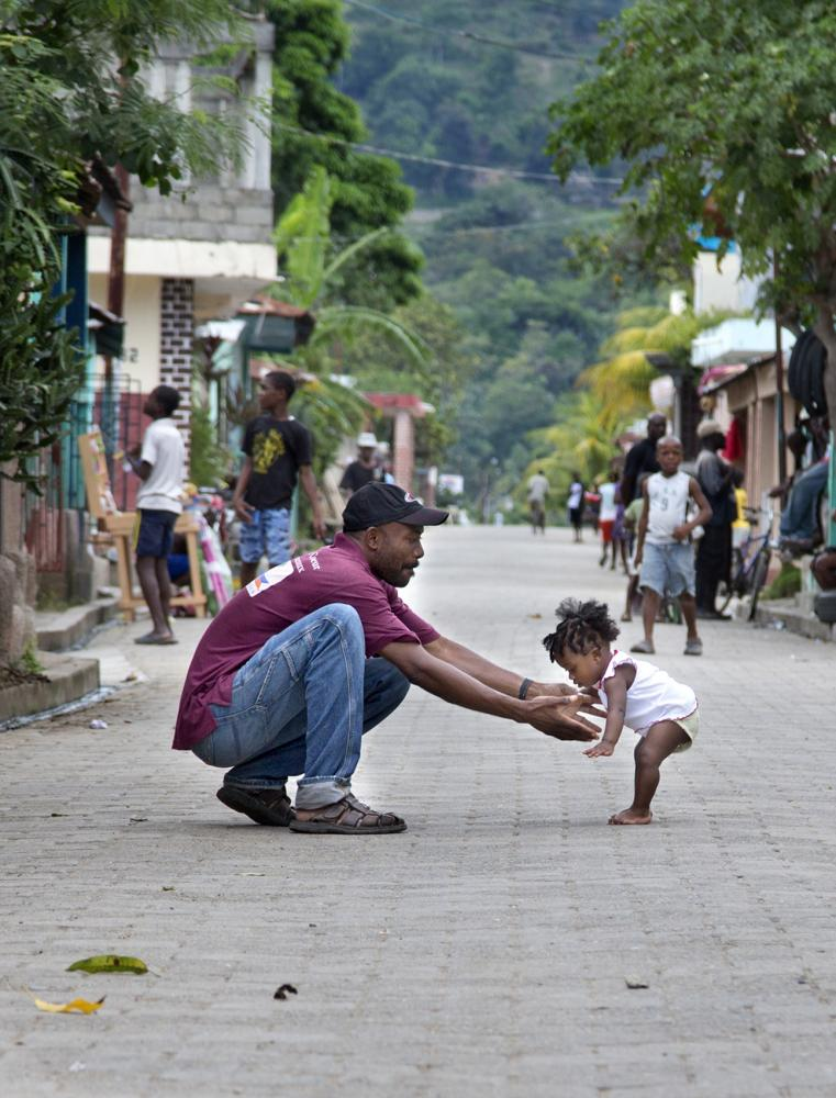 A father guides his daughter learning how to walk in Milot, Haiti.
