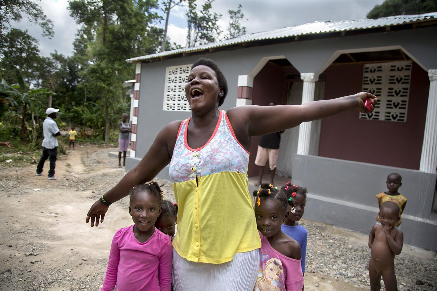 A woman celebrates moving into her new house with her family in Milot, Haiti. The house was paid for by a $5000 donation from a visiting physician.
