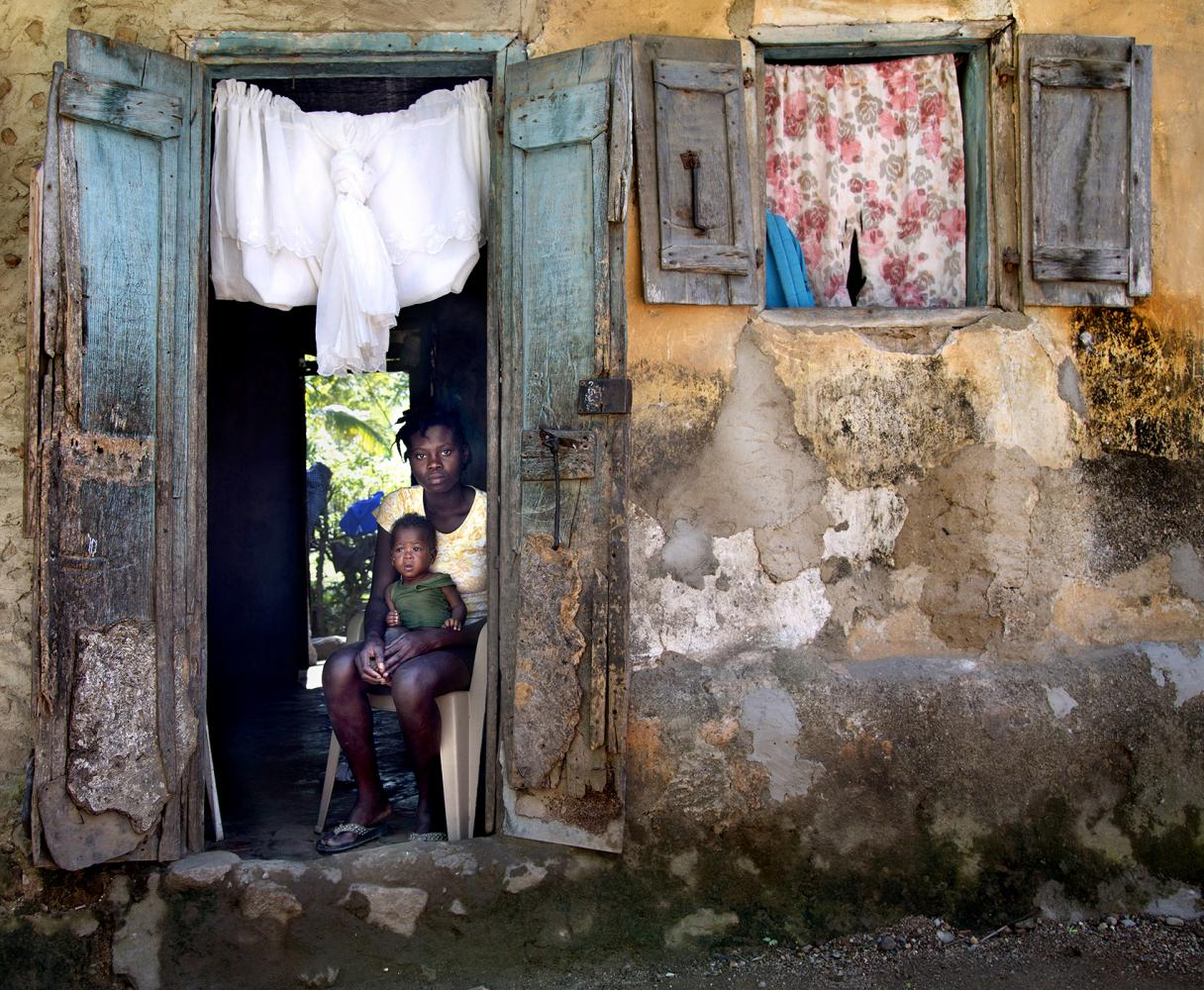 A woman and her baby sit in the doorway of their home in Milot, Haiti.