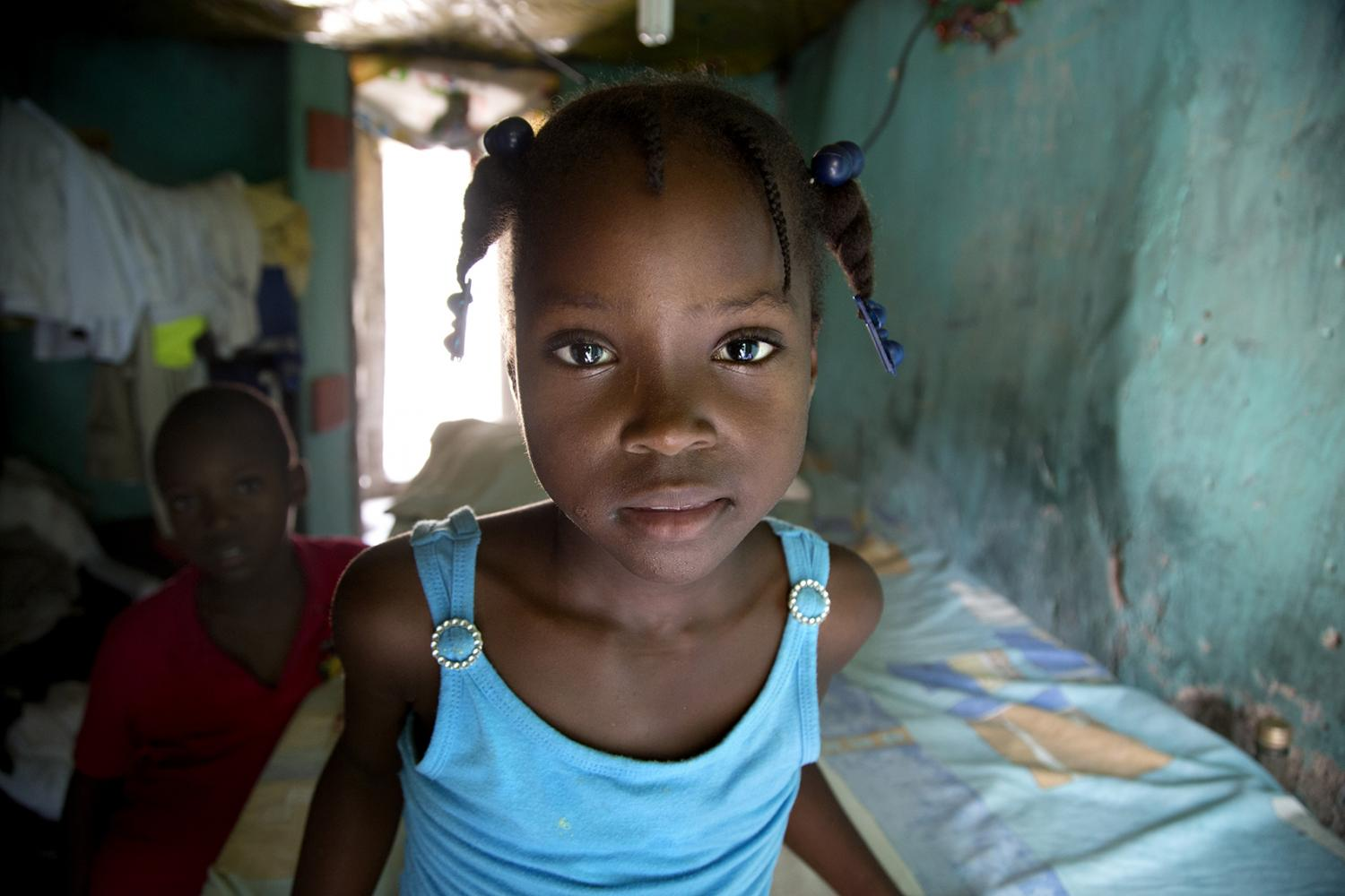 A little girl posing in the doorway of her home in Milot, Haiti.