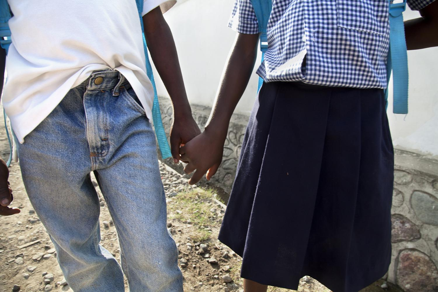 A brother and sister hold hands as they walk to school in Milot, Haiti.