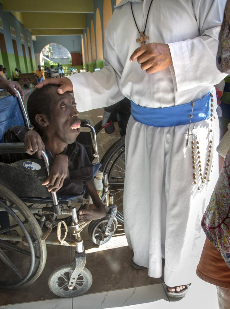 A brother shows compassion to a handicapped resident at an asylum in Cap Haitien, Haiti.