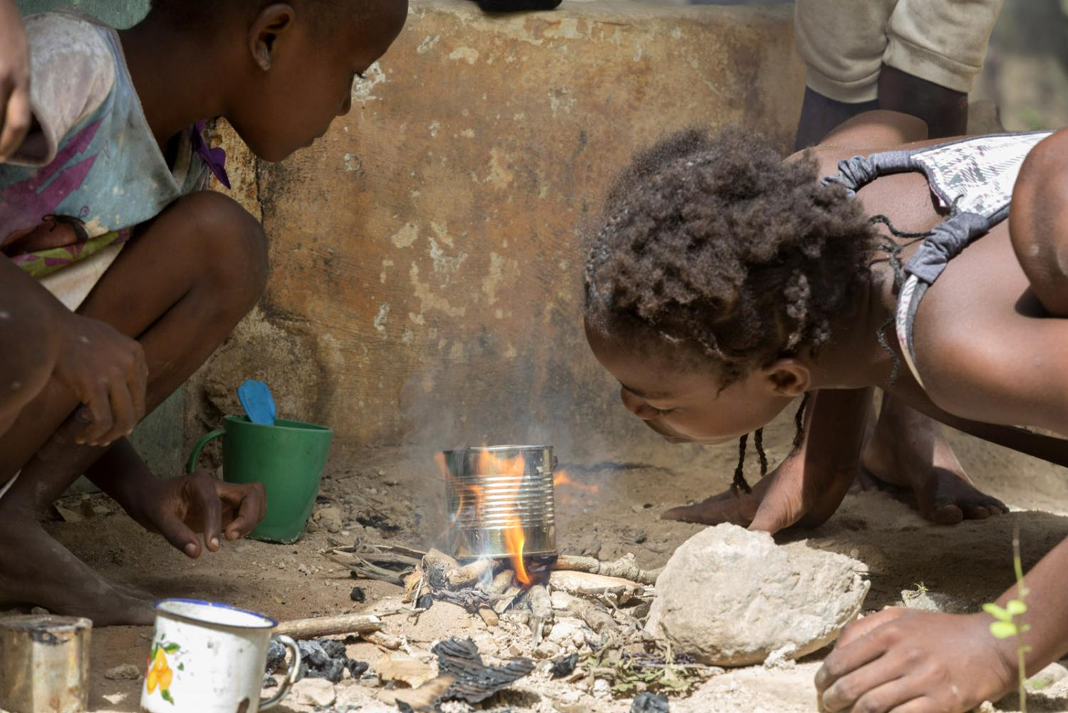 Little girls play kitchen buy lighting a small fire and putting a can over it in Milot, Haiti.